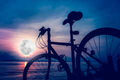 Silhouette of bicycle on the beach against beautiful full moon i Stock Photo
