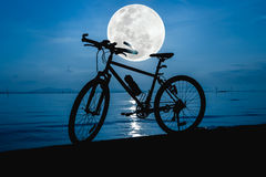 Silhouette of bicycle on the beach against beautiful full moon i Stock Photos