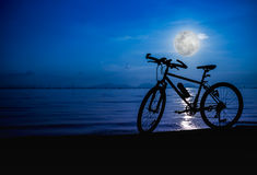 Silhouette of bicycle on the beach against bright full moon. Out Stock Images
