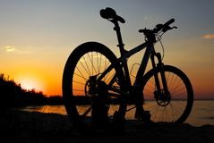 Silhouette of bicycle on the beach against colorful sunset. In the sea, gold sky background. Reflection of sun in water. Outdoors Royalty Free Stock Photo