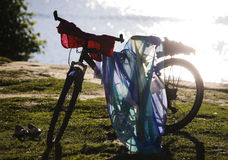 Silhouette of bicycle leaved on coast with clothes Stock Photography