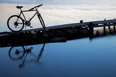Silhouette of a bicycle reflecting on the water. Silhouette of a bicycle reflecting on the sea water Royalty Free Stock Photos