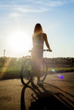 Silhouette of bicycle young woman stock images