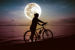 Silhouette of bicyclist enjoying the view at seaside. Outdoors. Stock Photo
