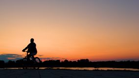 A teenager early in the morning at dawn or in the evening at sunset on a bicycle rides past a river or lake. Silhouette of a bicyc. Silhouette of a bicyclist guy stock video footage