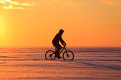 Silhouette of a bicyclist at sunset. Stock Images