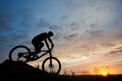 Silhouette of bicyclist wearing helmet and sportswear on mountain bike coming down the hill at sunset stock photography