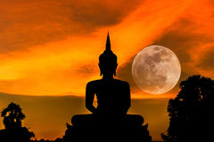 Silhouette big buddha statue on sunset with full moon background Stock Image
