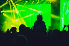 Silhouette of a big crowd at concert against a brightly lit stage. Night time rock concert with people having fun lifting hands up stock photos