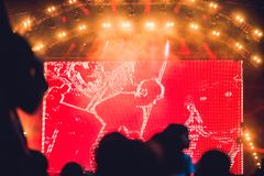 Silhouette of a big crowd at concert against a brightly lit stage. Night time rock concert with people having fun royalty free stock images