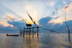 Silhouette big fish net traps and fisherman in the dawn. Royalty Free Stock Photo