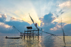 Silhouette big fish net traps and fisherman in the dawn. Stock Photos