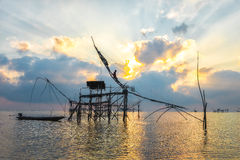 Silhouette big fish net traps and fisherman in the dawn. Royalty Free Stock Photos
