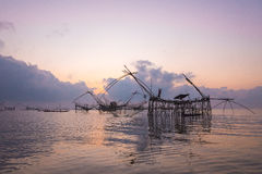 Silhouette big fish net traps and fisherman in the dawn. Royalty Free Stock Photography