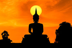Silhouette big golden buddha statue sitting on sunset Stock Photo