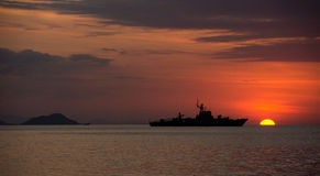 Silhouette of big ship on the ocean at nightfall with orange sunset. Royalty Free Stock Image