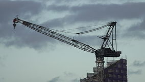 Silhouette of a big tower crane above a building stock video footage