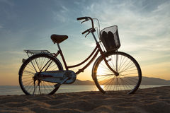 Silhouette of a bike Sea. Silhouette of an old bicycle stands on the beach at sunrise stock photography