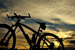 Silhouette of a bike on sky background. Stock Image