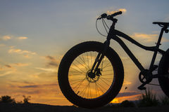 Silhouette of a bike on sunset Stock Photos