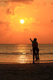Silhouette of a biker on the beach. Point to sunset stock photos