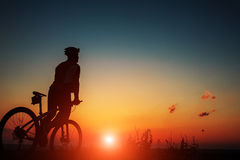 Silhouette of a biker and bicycle on sky background. Stock Photo