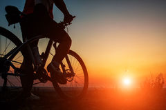 Silhouette of a biker and bicycle on sky background. Royalty Free Stock Photo