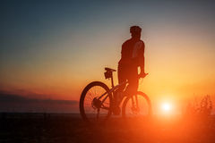 Silhouette of a biker and bicycle on sky background. Stock Image