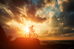 Silhouette of a biker and bicycle on sky background. Royalty Free Stock Photography