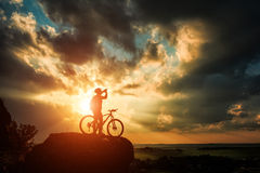 Silhouette of a biker and bicycle on sky background. Stock Photos