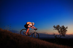 Silhouette of a biker and bicycle on sunset background. Royalty Free Stock Photos