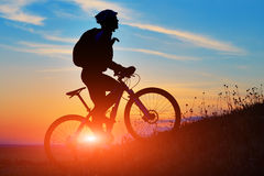 Silhouette of a biker and bicycle on sunset background. Royalty Free Stock Image