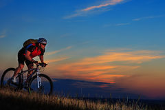 Silhouette of a biker and bicycle on sunset background. Stock Photos