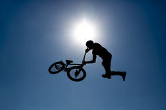 Silhouette biker blue sky. Silhouette of a biker jumping against the blue sky and the sun Stock Image