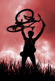 Silhouette of a biker holding his bicycle royalty free stock photos