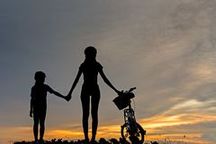 Silhouette biker lovely family at sunset over the ocean. Mom and daughter bicycling at the beach. stock photos
