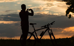 Silhouette of biker at sunset Royalty Free Stock Images