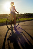 Silhouette of biker woman. Back view silhouette of sporty beautiful young woman on bike wearing casual white tank top and jeans shorts on summer day, sun shining stock photography