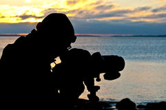 Silhouette of a birdwatcher. Looking out over the ocean at sunset/sunrise stock photo