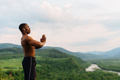 Silhouette of black african american muscular man with hands raised to beautiful mountain background. Amen Pray concept. Royalty Free Stock Photography