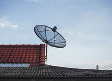 Silhouette black satellite dish on the roof. Stock Photos