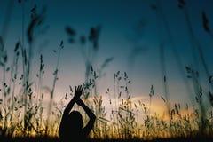 Silhouette bleue de fille de contre-jour sur le champ photo stock