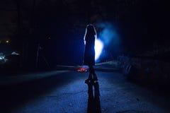 Silhouette bleue de fille pendant la nuit de rue Photos libres de droits