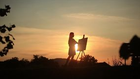 Silhouette of a blonde girl paints a painting on the canvas with the help of paints. A wooden easel keeps the picture stock footage