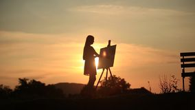Silhouette of a blonde girl paints a painting on the canvas with the help of paints. A wooden easel keeps the picture stock video footage