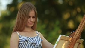 Beautiful girl draws a picture in the park using a palette stock footage