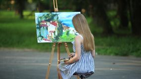 Beautiful girl draws a picture in the park using a palette. Silhouette of a blonde girl paints a painting on the canvas with the help of paints. A wooden easel stock video