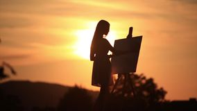 Silhouette of a blonde girl paints a painting on the canvas with the help of paints. A wooden easel keeps the picture stock video