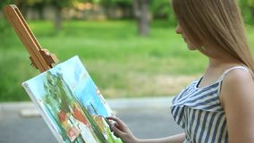 Beautiful girl draws a picture in the park using a palette. Silhouette of a blonde girl paints a painting on the canvas with the help of paints. A wooden easel stock footage