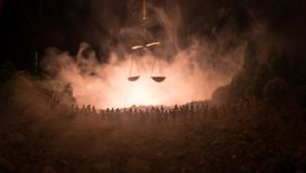 Silhouette of blurred giant scale of justice behind crowd at night with foggy fire background. Selective focus royalty free stock images